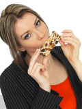 Young Business Woman Eating a Breakfast Cereal Bar Royalty Free Stock Image