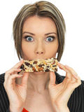 Young Business Woman Eating a Breakfast Cereal Bar Stock Image