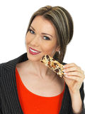 Young Business Woman Eating a Breakfast Cereal Bar Royalty Free Stock Photography