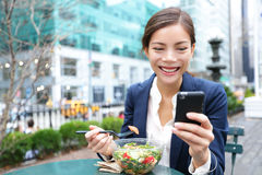 Young business woman eating salad on lunch break. In City Park living healthy lifestyle working on smart phone. Happy smiling multiracial young businesswoman royalty free stock photos