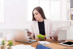 Young business woman eating salad at office. Having healthy lunch at workplace while using phone and reading papers royalty free stock images