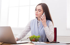 Young business woman eating salad at office Stock Photography