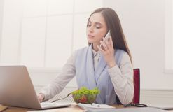 Young business woman eating salad at office Stock Photo