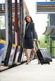 Young business woman embarking on train. With suitcase royalty free stock photo