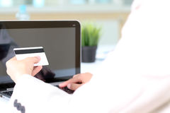 Young business woman  entering  data of  a credit card . On-line Royalty Free Stock Photos