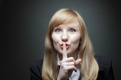 Young business woman with finger on lips Stock Image