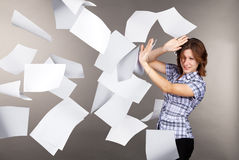 Young business woman with flying documents Royalty Free Stock Photography