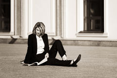 Young business woman with a folder sitting on sidewalk Royalty Free Stock Photography