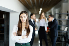 Young business woman in front of discussing coworkers. Young business women in front of discussing coworkers in modern office Stock Photography