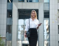 Young business woman in front of office building using her cell phone stock photos