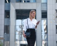 Young business woman in front of office building using her cell phone royalty free stock image