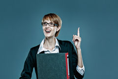 Young business woman gesturing with her finger and holding a folder Royalty Free Stock Photos
