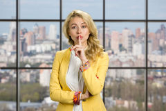 Young business woman gesturing silence. Beautiful young office manager making silence gesture on business center window background Stock Photos