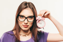 The young business woman in glasses with alarm clock. Stock Images