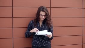 Young business woman was upset after reading the documents standing next to the office. Young business woman in glasses and dark clothes was upset after reading stock footage