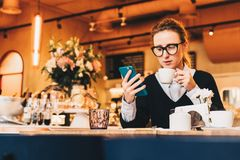 Young business woman in glasses sits in cafe at table, uses smartphone, drinking coffee. Girl working, chatting Royalty Free Stock Photos
