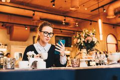 Young business woman in glasses sits in cafe at table, uses smartphone, drinking coffee. Girl working, chatting Stock Photos