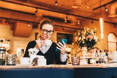 Young business woman in glasses sits in cafe at table, uses smartphone, drinking coffee. Girl working, chatting Stock Photography