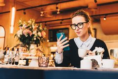 Young business woman in glasses sits in cafe at table, uses smartphone, drinking coffee. Girl working, chatting Royalty Free Stock Images