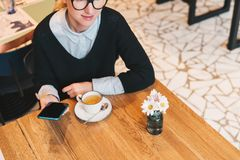 Young business woman in glasses sits in cafe at table, uses smartphone, drinking coffee. Girl working Stock Image