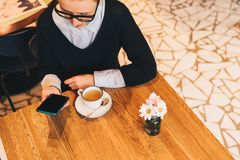 Young business woman in glasses sits in cafe at table, uses smartphone, drinking coffee. Girl working Royalty Free Stock Photos