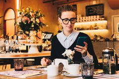 Young business woman in glasses sits in cafe at table, uses smartphone. On table is cup of coffee. Girl working Royalty Free Stock Images