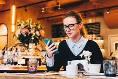 Young business woman in glasses sits in cafe at table, uses smartphone. On table is cup of coffee. Girl working. Chatting, blogging, checking email. Online Royalty Free Stock Photography