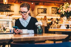 Young business woman in glasses sits in cafe at table, uses smartphone. On table is cup of coffee. Girl working Stock Photos