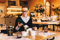 Young business woman in glasses sits in cafe at table, uses smartphone. On table is cup of coffee. Girl working Stock Image