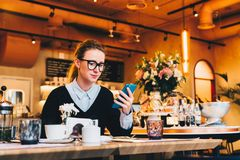 Young business woman in glasses sits in cafe at table, uses smartphone. On table is cup of coffee. Girl working Stock Photography