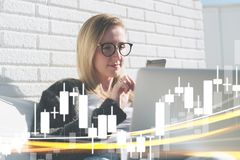 Young business woman in glasses sits at laptop and uses smartphone. In foreground charts of binary options. Royalty Free Stock Images