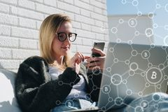 Young business woman in glasses sits at laptop and uses smartphone. In foreground infographics, bitcoin icons. Royalty Free Stock Image