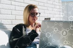 Young business woman in glasses sits at laptop and uses smartphone. In foreground infographics, bitcoin icons. Royalty Free Stock Photo