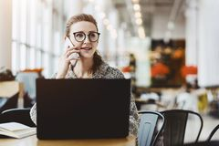 Young business woman in glasses sitting at table in cafe, talking on cell phone while working on laptop.Student learning. Young business woman in glasses sitting stock images