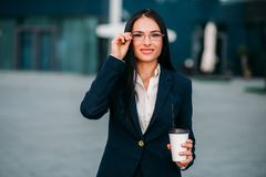Young business woman in glasses and suit. Portrait of young, beautiful business woman in glasses and suit with laptop in hands. Modern building, financial center Stock Photography