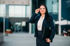 Young business woman in glasses and suit. Portrait of young, beautiful business woman in glasses and suit with laptop in hands. Modern building, financial center Stock Photos