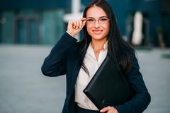 Young business woman in glasses and suit. Portrait of young, beautiful business woman in glasses and suit with laptop in hands. Modern building, financial center Stock Photo