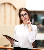 Young business woman in glasses with tablet standing indoors