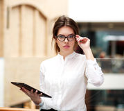 Young business woman in glasses with tablet standing indoors Royalty Free Stock Photo