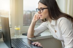 Young business woman with glasses working on laptop computer at home, in hotel, talking on video, working remotely.  royalty free stock photo