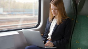 Young Business Woman Goes by Train, Works on a Laptop and Looks at the Window stock video footage