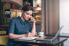 Young business woman in gray dress sitting at table in cafe, talking oncell phone while taking notes in notebook. Stock Photo