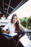 Young business woman sitting at table in cafe, talking oncell phone while taking notes in notebook on table laptop. Student learni. Young business woman in gray stock photography