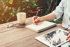 Young business woman hand with pencil writing on notebook. Woman Stock Image