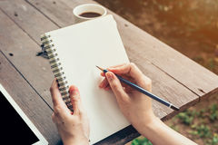 Young business woman hand with pencil writing on notebook. Woman Stock Images