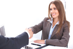 Young business woman handshaking sitting at the desk on office background, copy space area at the left upper corner Stock Image