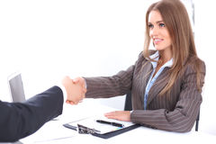 Young business woman handshaking  sitting at the desk on office background, copy space area at the left upper corner Royalty Free Stock Photos