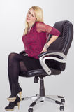 Young business woman having back pain. While sitting in office chair, painful face expresion Stock Images
