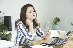 Young business woman having a neck pain. stock image