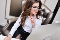 Beautiful business woman in a white shirt and glasses at the workplace at the computer monitor. Young business woman head sits at a desk in a leather chair Royalty Free Stock Image
